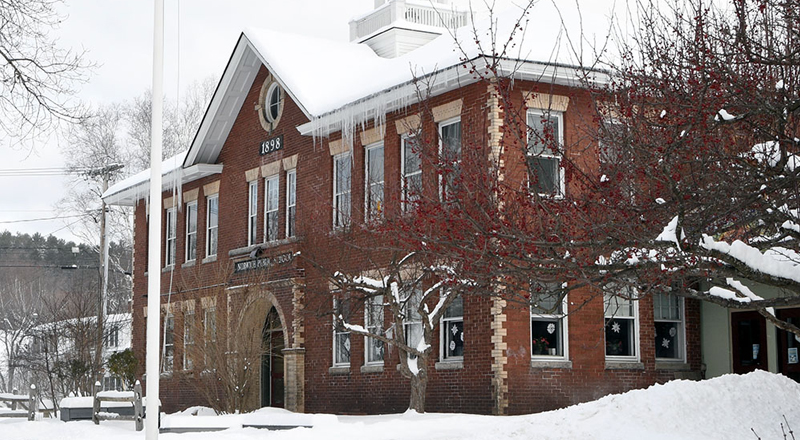 Marion Cross School building front with snow on the ground